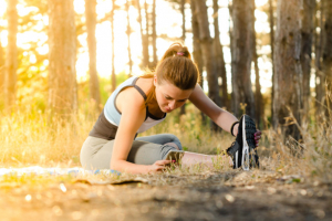 A woman stretching and exercising in the woods